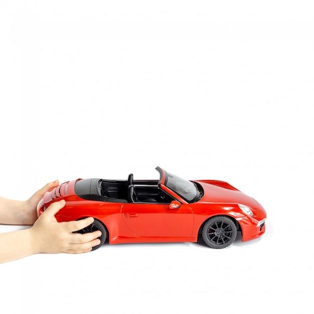Mãos de bebê segurando o carro vermelho do brinquedo isolado no fundo branco Foto Premium