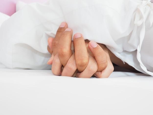 Mãos de casal amantes fazendo sexo em uma cama de manhã com luxúria e amor Foto Premium