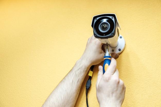 Mãos de close-up do técnico que ajusta a câmera do cctv Foto Premium