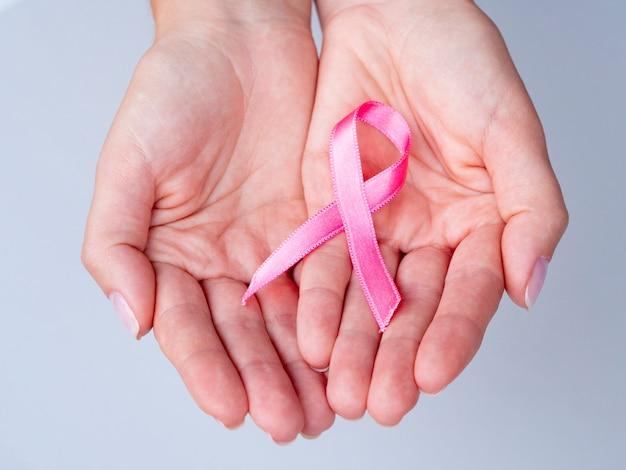 Mãos de close-up, segurando a fita rosa Foto gratuita