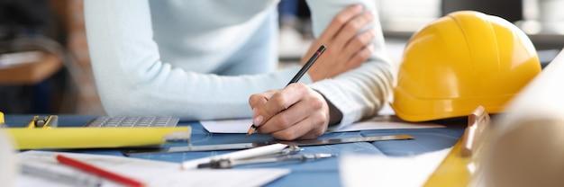 Mãos de construtor designer desenhar desenho na mesa. desenvolvimento no campo do conceito de construção Foto Premium