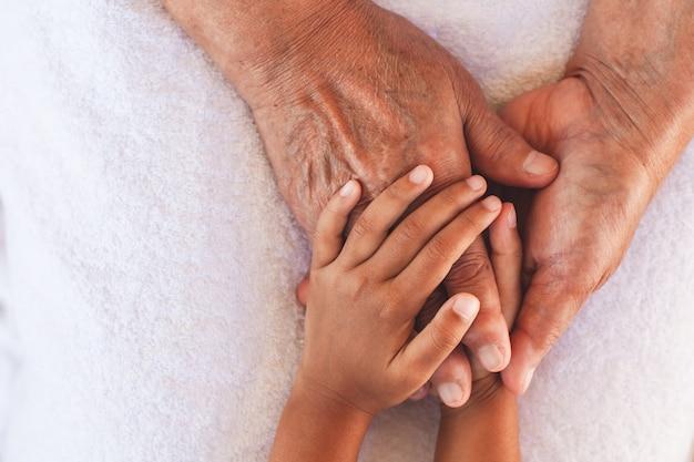 Mãos, de, criança asian menina, segurando, idoso, mãos avô, enrugado, pele, com, sentimento, cuidado, e, amor Foto Premium
