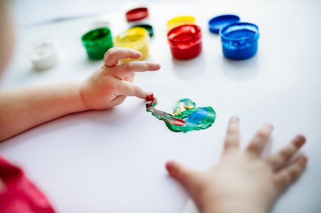 Mãos de criança começam a pintar na mesa com materiais de arte Foto Premium