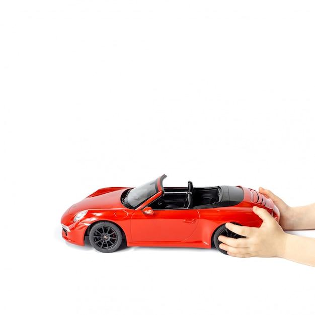 Mãos de crianças segurando um carro de brinquedo modelo porsche carrera s 911 vermelho isolado Foto Premium
