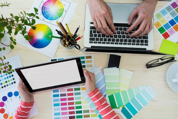 Mãos de designers gráficos que usam o portátil e tabuleta digital Foto gratuita