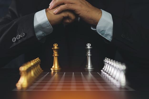 Mãos de empresário na suíte preta, sentado e segurando as mãos, planejando a estratégia com xadrez na mesa vintage. conceito de objetivo de decisão e conquista. Foto Premium