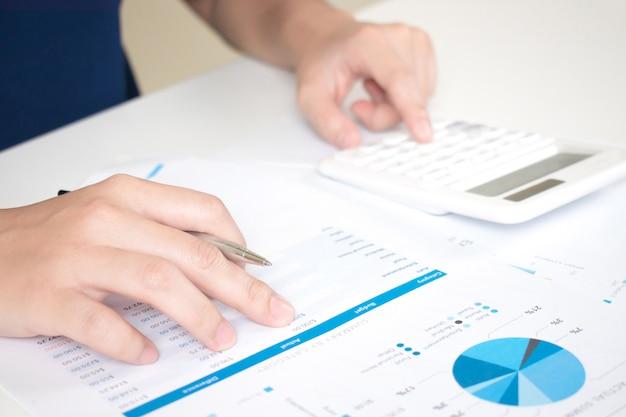 Mãos de empresários trabalhando na mesa usando uma calculadora para calcular os números. Foto Premium