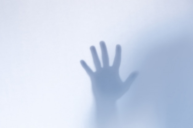 Mãos de fantasma assustador desfocado por trás de um copo branco Foto Premium