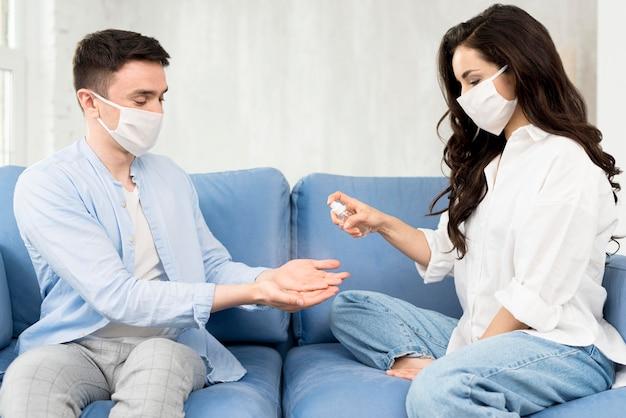 Mãos de higienização de casal em casa Foto gratuita