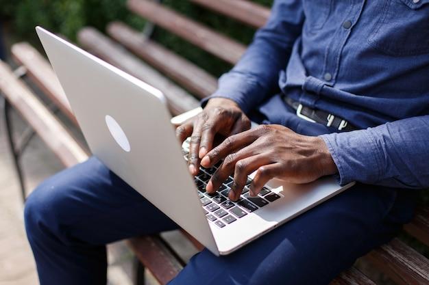Mãos, de, homem americano africano, digitando, algo, ligado, a, laptop, enquanto, ele, senta-se, ligado, a, banco Foto gratuita