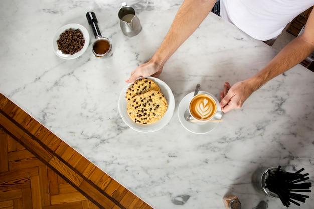 Mãos de homem com biscoitos e um cappuccino no balcão Foto gratuita