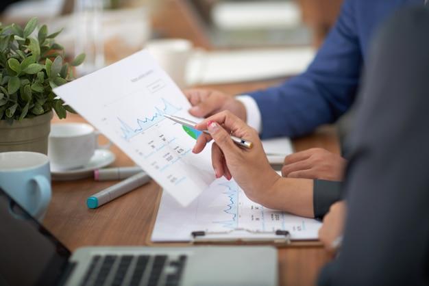 Mãos de homem e mulher em trajes profissionais, sentado na mesa no escritório e discutir o gráfico Foto gratuita