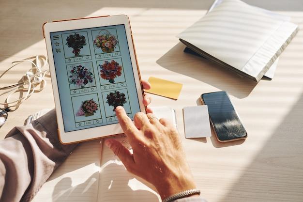 Mãos de homem irreconhecível, selecionando o buquê de flores on-line no tablet Foto gratuita