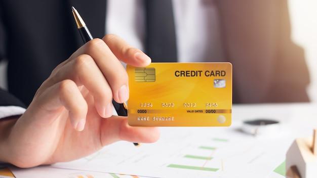 Mãos, de, homem negócios, segurando, cartão crédito, com, financeiro, documentos, financeiro, conceito Foto Premium