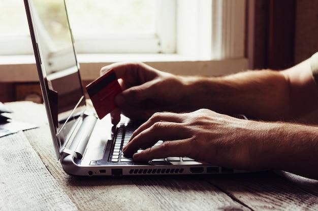 Mãos de homem segurando o cartão de crédito e usando o laptop à noite. Foto Premium