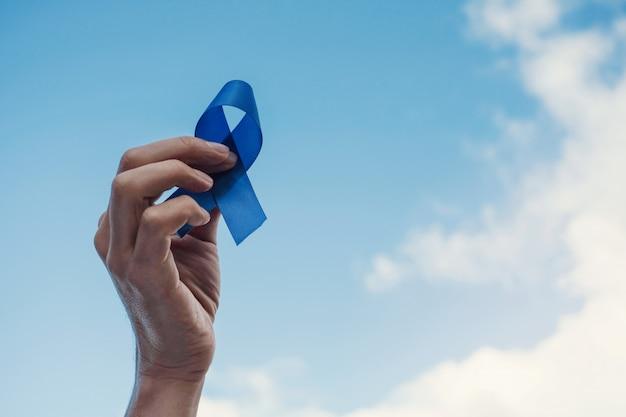 Mãos de homem segurando uma fita azul sobre o céu azul, conscientização do câncer de próstata, novembro azul Foto Premium