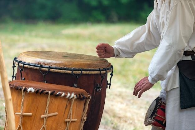 Mãos de homem tocando tambor de couro ao ar livre. Foto Premium