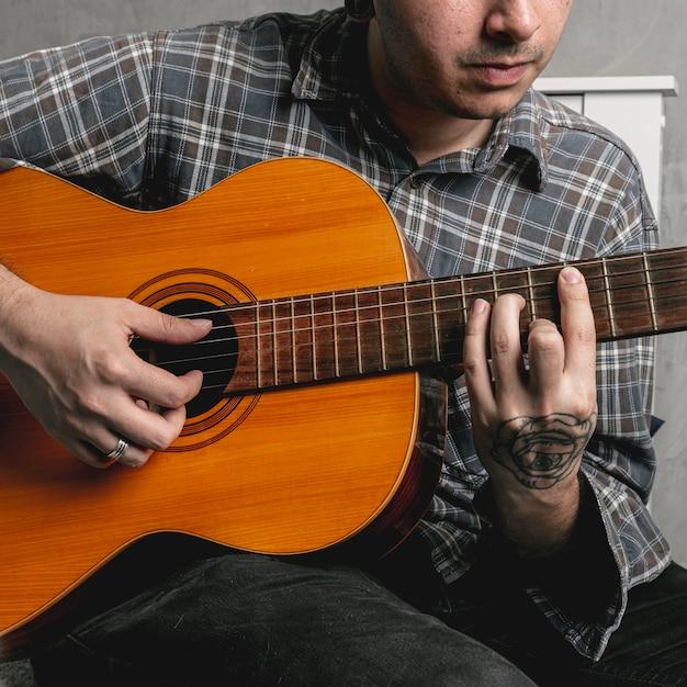 Mãos de homem tocando violão Foto gratuita