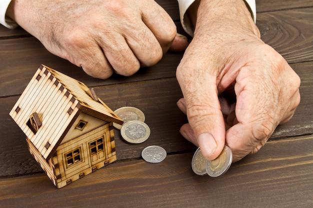 Mãos de homem velho e uma casa modelo com as moedas na mesa Foto Premium