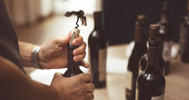 Mãos de homens abrem uma garrafa de vinho com um saca-rolhas Foto Premium