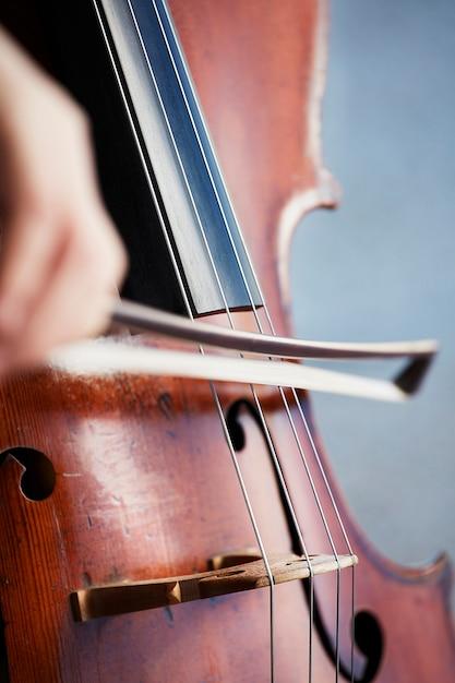 Mãos de jogador violoncelista. violoncelista tocando violoncelo no fundo do campo. arte musical, paixão pelo conceito de música. música clássica violoncelista profissional solo executar Foto gratuita