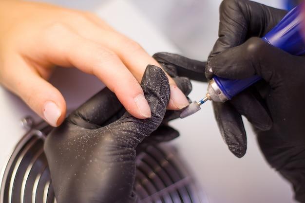 Mãos de manicure em luvas pretas e unhas do cliente. mulher no salão de beleza. Foto Premium