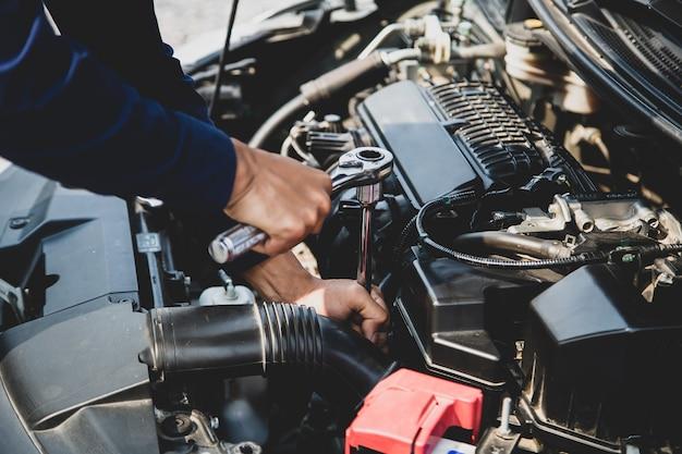Mãos de mecânico de automóveis usando a chave para reparar um motor de carro. Foto Premium