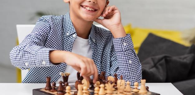 Mãos de menino jogando xadrez Foto gratuita