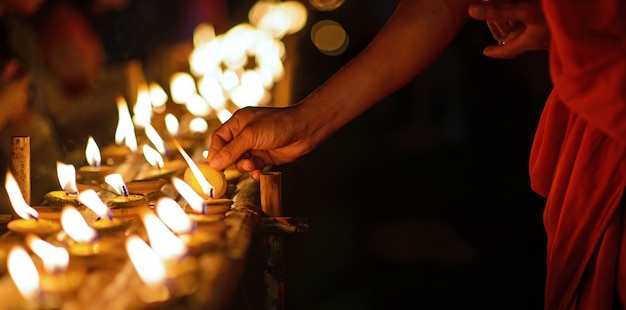 Mãos de monge budista segurando a taça de vela no escuro, chiang mai, tailândia Foto Premium
