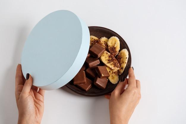 Mãos de mulher, abrindo a caixa com chocolate e banana em branco Foto gratuita