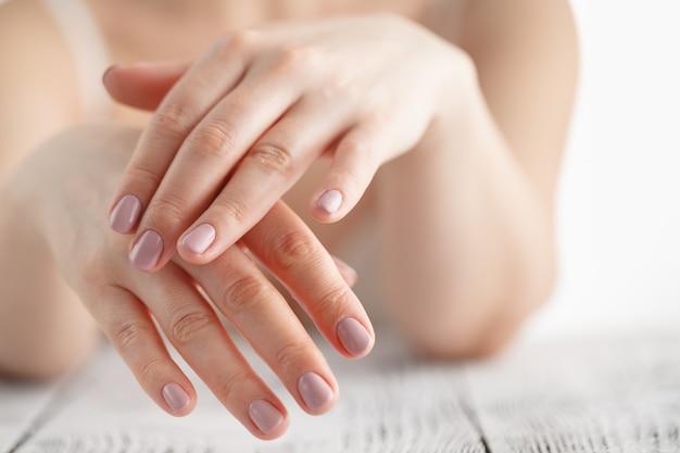 Mãos de mulher, aplicar creme hidratante para a pele Foto Premium