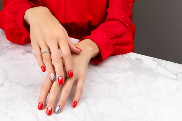 Mãos de mulher bem cuidadas com desenho de unhas de natal em fundo cinza mármore Foto Premium