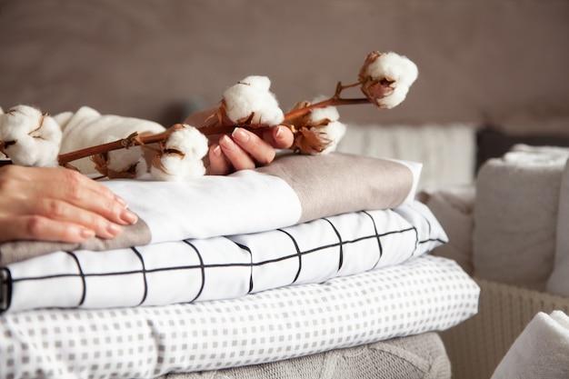 Mãos de mulher bem cuidadas segurando um galho de algodão com uma pilha de lençóis, cobertores e toalhas dobrados cuidadosamente. produção de fibras têxteis naturais. fabricação. produto orgânico. Foto Premium