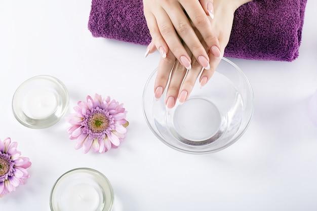 Mãos de mulher com lindas unhas de manicure francesa Foto Premium