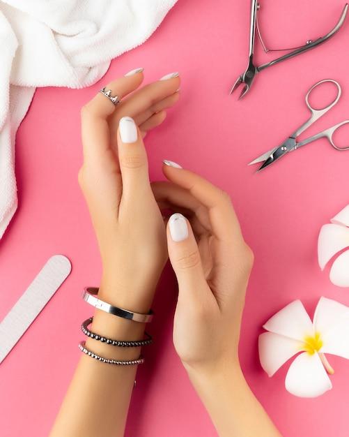 Mãos de mulher com manicure francesa branca na moda Foto Premium