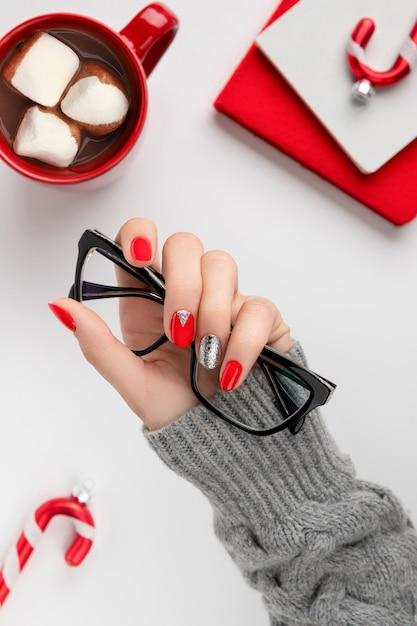 Mãos de mulher com manicure vermelha na moda segurando óculos Foto Premium