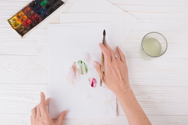 Mãos de mulher com pincel perto de papel com borrões, vidro e conjunto de cores de água Foto gratuita