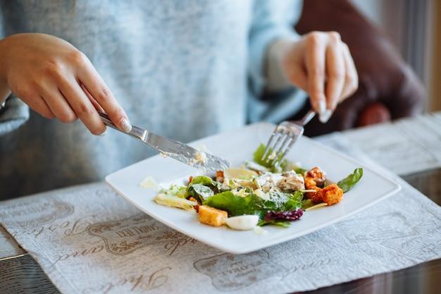 Mãos de mulher com salada caesar na mesa no restaurante Foto gratuita