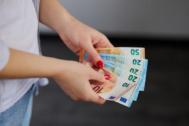Mãos de mulher contando dinheiro euro, segurando nas mãos dela. Foto Premium