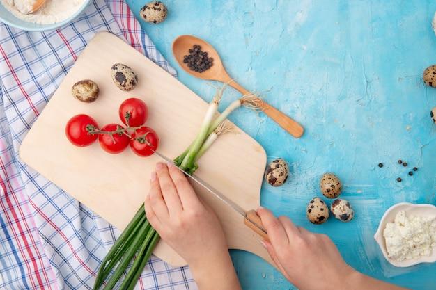Mãos de mulher, corte a cebolinha e outros alimentos e legumes na mesa azul Foto gratuita