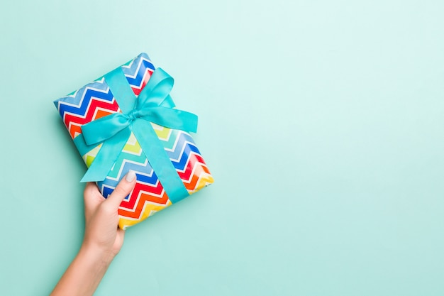 Mãos de mulher dão embrulhado natal ou outro presente artesanal de férias em fundo de papel colorido Foto Premium