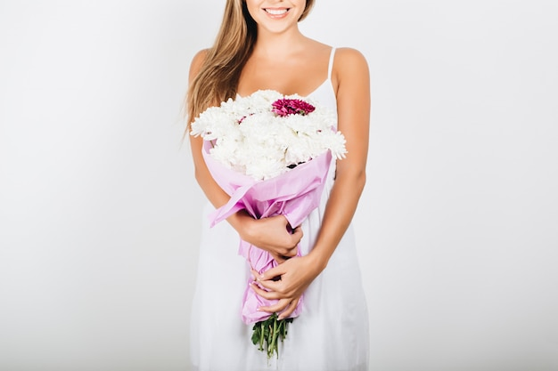 Mãos de mulher delicada close-up segurando ramo de flores Foto gratuita