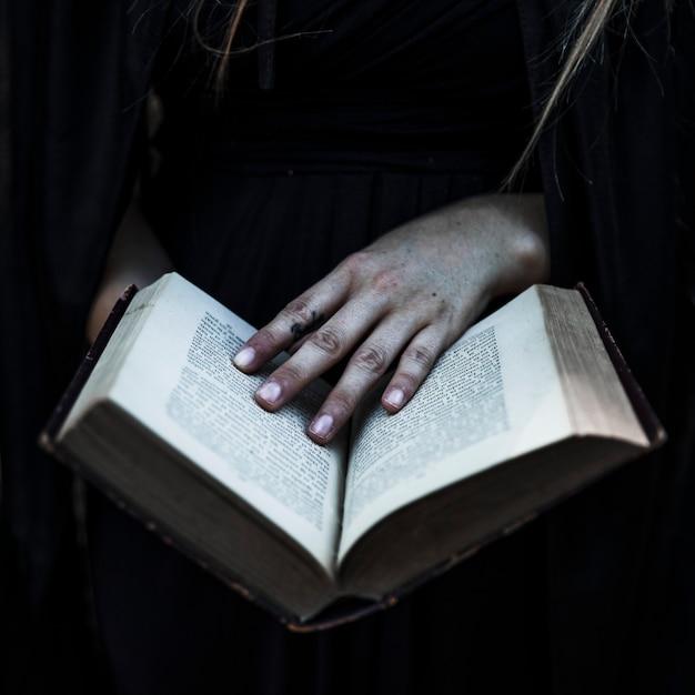 Mãos de mulher em roupas pretas, segurando o livro aberto Foto gratuita