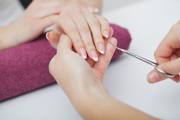 Mãos de mulher em um salão de beleza recebendo um procedimento de manicure Foto Premium