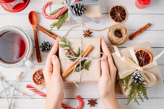Mãos de mulher embrulhando caixa de presente com decorações de natal em uma vista superior de madeira, branca Foto Premium
