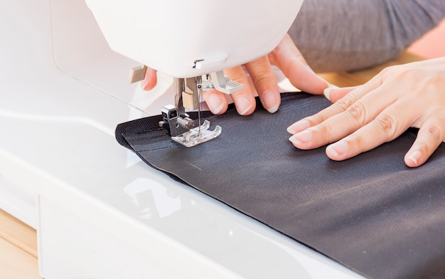 Mãos de mulher, fazendo o patchwork usando a máquina de costura Foto gratuita