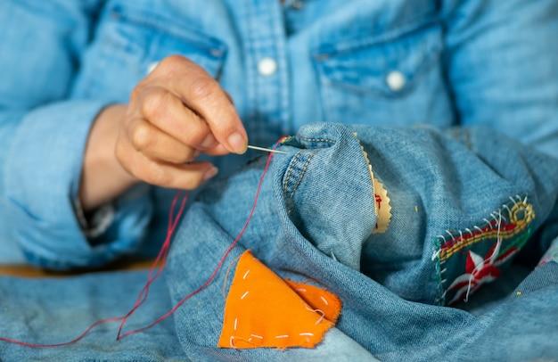 Mãos de mulher idosa costura em jeans de tecido Foto Premium