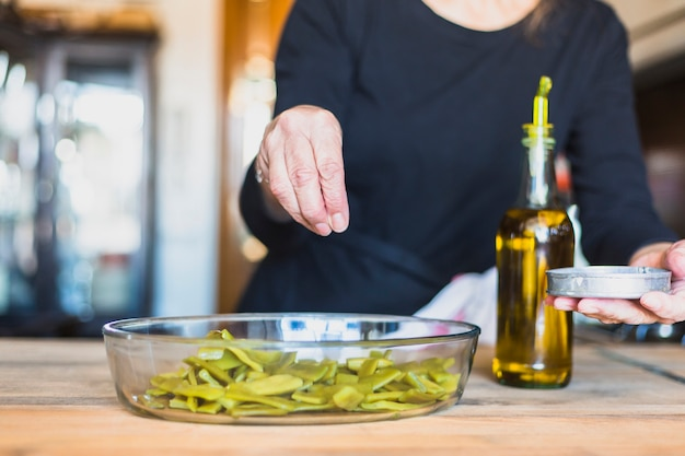 Mãos, de, mulher idosa, cozinhar, em, cozinha Foto gratuita