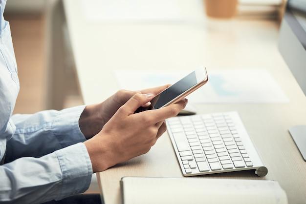 Mãos de mulher irreconhecível usando smartphone na mesa no escritório Foto gratuita