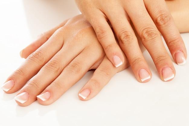 Mãos de mulher jovem com manicure francesa Foto gratuita